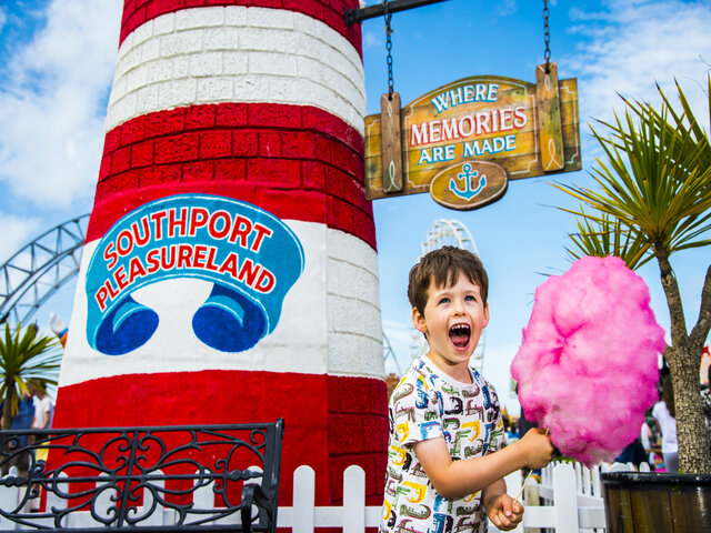 boy holding candy floss in front of a red and white striped lighthouse