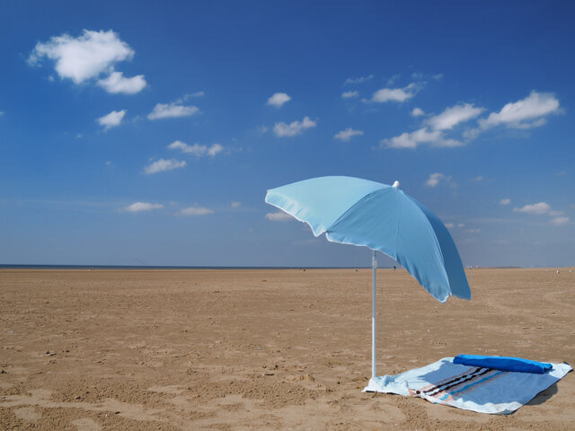 light blue parasol and white towel on an empty beach