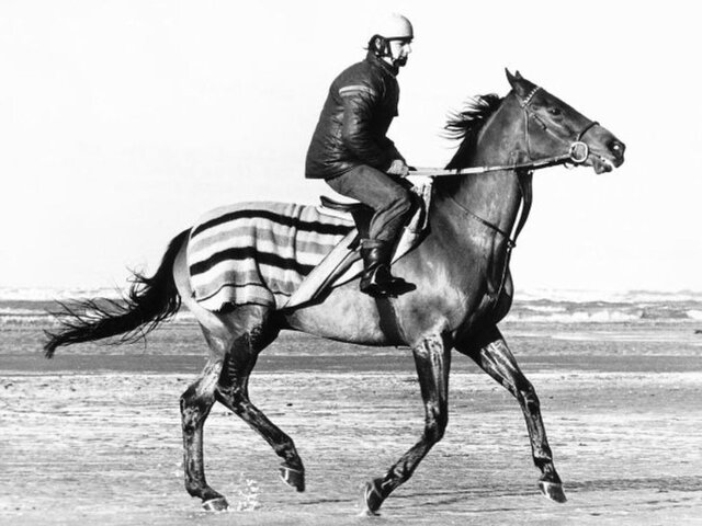 black and white picture of Red Rum and jockey on Southport beach