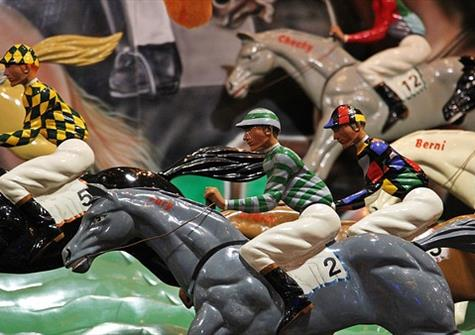 toy horses and riders from a fairground horse racing game